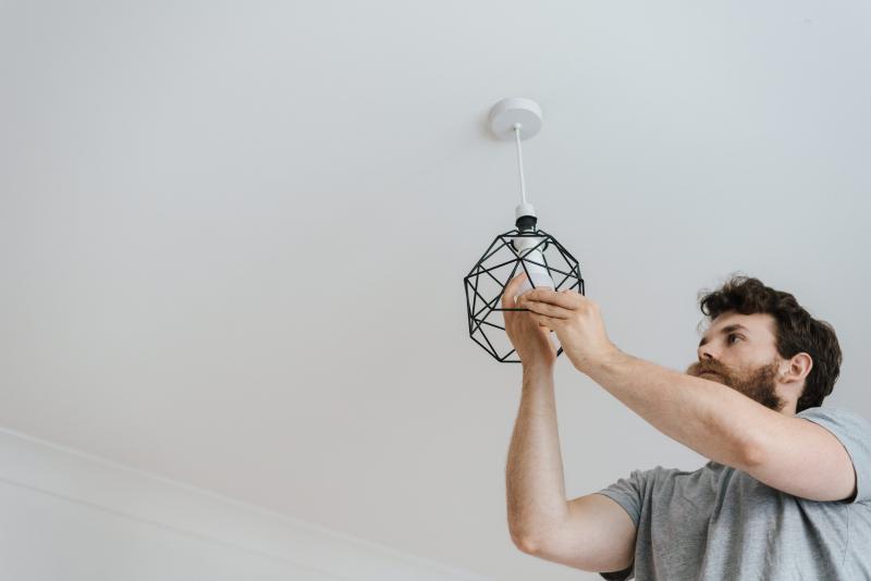 bearded man replacing bulbs with LED