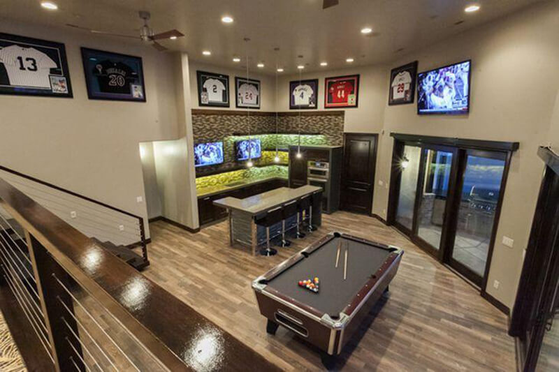 View of Man Cave from stairs, pool table and tv on wall