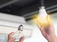 Hand with a lit light bulb